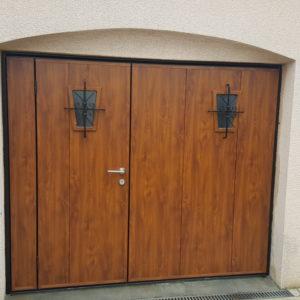 Porte de garage basculante MOOS, motif lames verticales coloris chêne doré, hublots avec grille forgé, porte équipée d'un portillon.