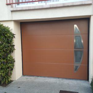 Porte de garage sectionnelle, panneau brun sablé, hublots.