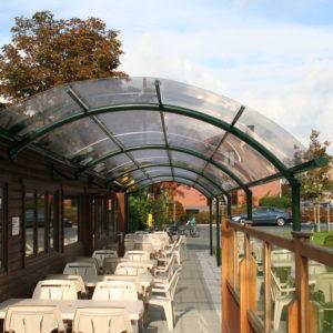 BOzARC arrondi pour terrasse restaurant, structure aluminium vert foncé, toiture transparente.