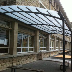 BOzARC descendant, toiture polycarbonate compact opalin, structure aluminium gris foncé, cour d'école.
