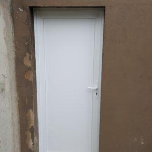 Porte de service en PVC blanc, un vantail, panneau plein.
