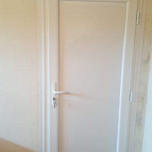 Porte de service en PVC blanc, un vantail, panneau plein, vue intérieure.